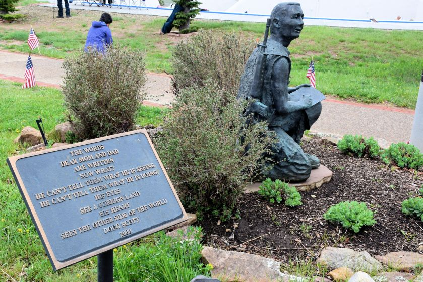 statue of a soldier in a small flower bed