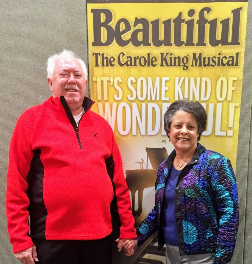 husband-wife couple holding hands in front of poster for Beautiful The Carole King Musical