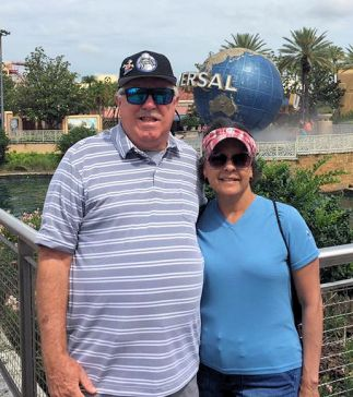 a man and woman standing in front of world globe at Universal Studios
