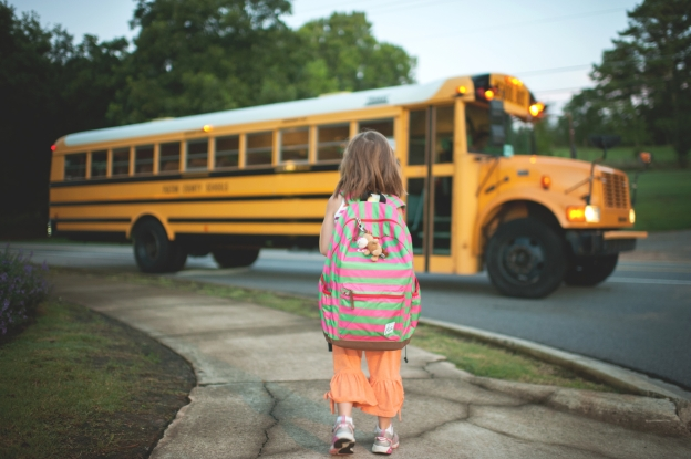 a little girl with a big backpack standing next to a yellow school bus