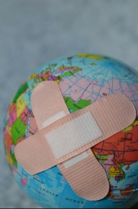 a world globe with two crossed bandaids