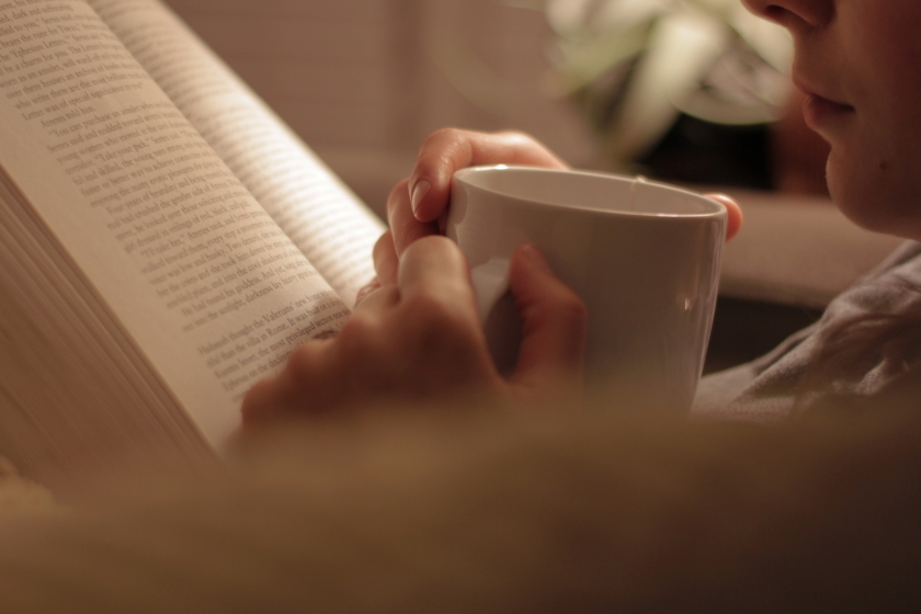 a man reading a book, holding a mug