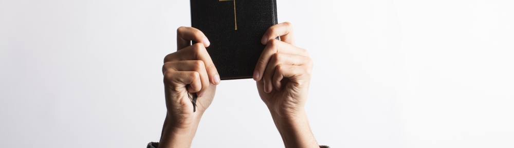 a Bible held up with two hands by unknown person
