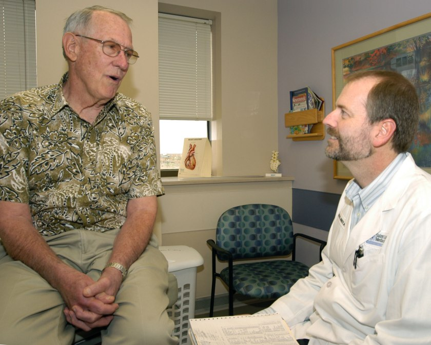 Michael Munger, M.D., consults a patient at his medical office in Overland Park, Kan.