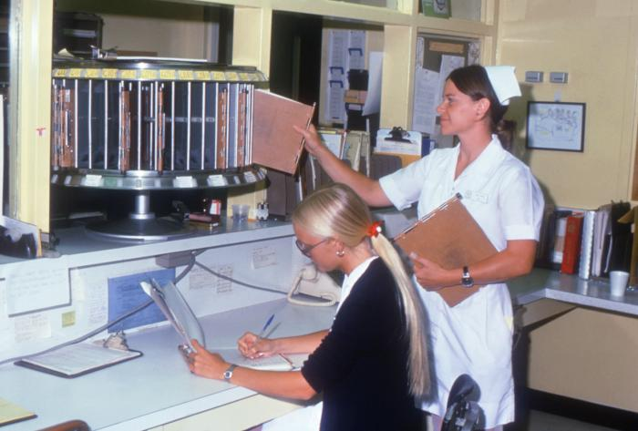 two hospital personnel working with patients' records at a nurse's station.
