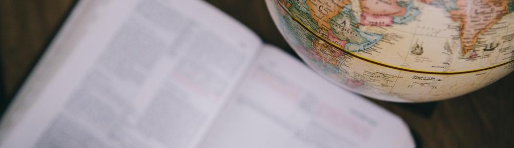 an open Bible next to a world globe