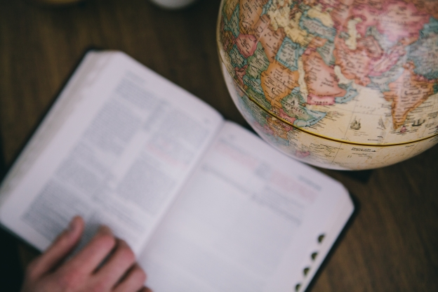an open Bible next to a world globe