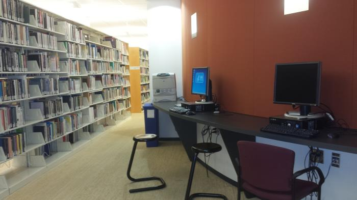 shelves in a library with adjacent computers
