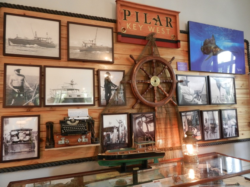 old photographs , a boat model, and a steering wheel, hanging on a wall at the Hemingway Home Museum
