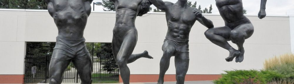 statue of 4 athletic people jumping in celebration