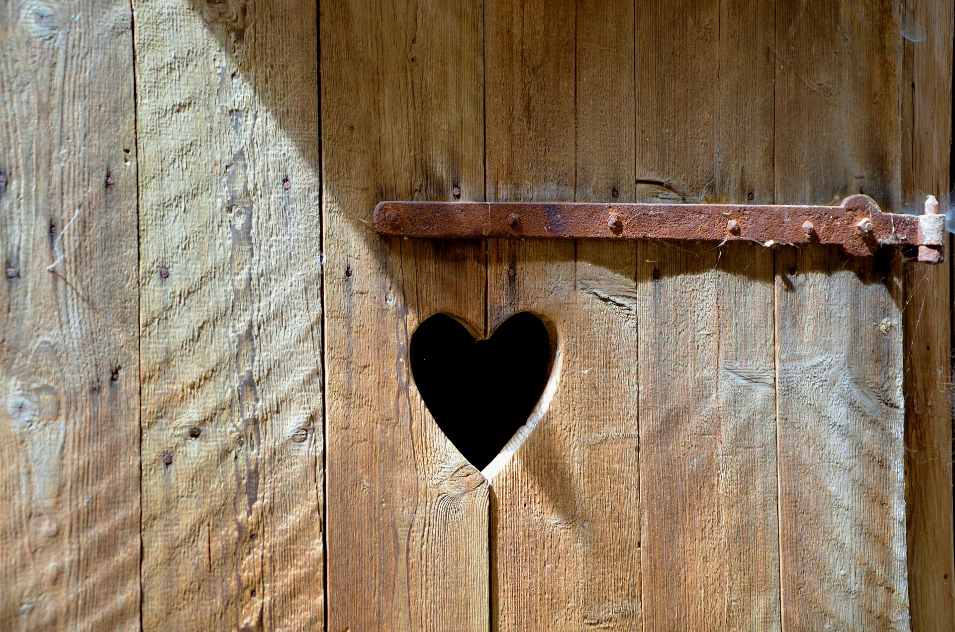 a wooden door with a heart shaped hold