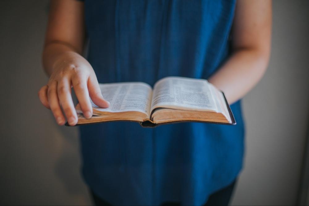 a woman holding an open Bible