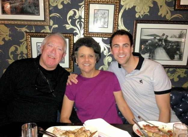 lady, 2 men posing together in a restaurant