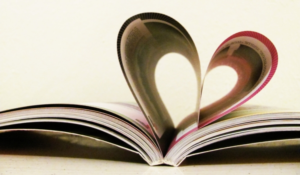 an open book with pages folded to make a heart