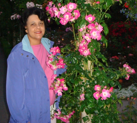 woman standing by pink flowers
