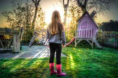 young girl in bright pink boots next to a pink playhouse in her yard