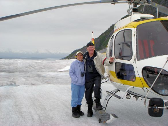 man and woman standing next to a helicopter on a glacier