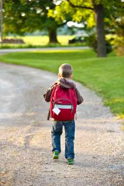 little boy walking down a dirt road with a red backpack