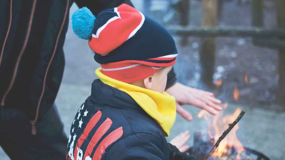 a boy and man holding their hands over a fire