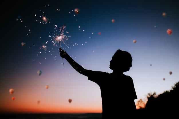 boy holding a sparkler at dawn