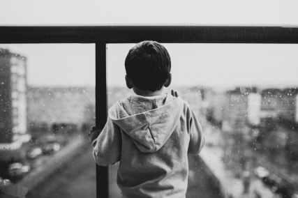 little boy in a hoody, looking out a rainy window