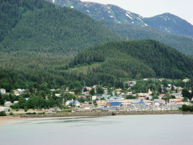 a village by the shore flanked by mountains, Alaska