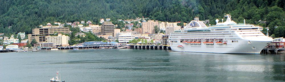 a cruise ship and a small tug boat in a mountainside port