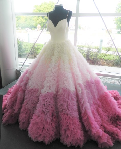 a floor length, fancy pink and white dress covered in ruffles on the skirt