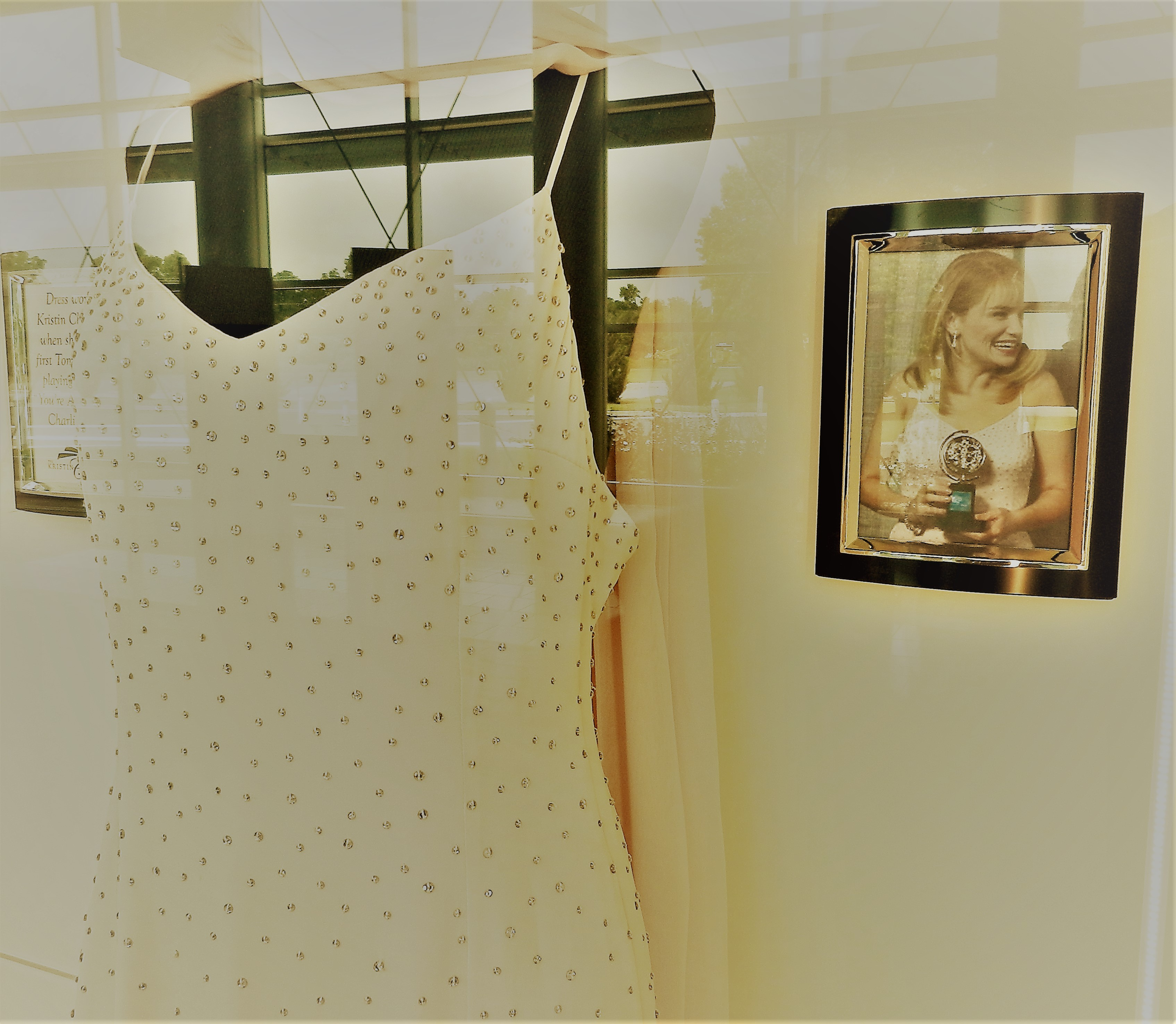 an evening gown on display next to a photo of Kristen Chenoweth