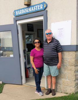 """a man and woman standing by a sign """"harbormaster"""
