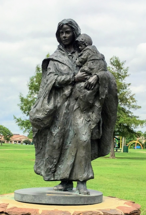 a bronze statue of a woman holding a small child