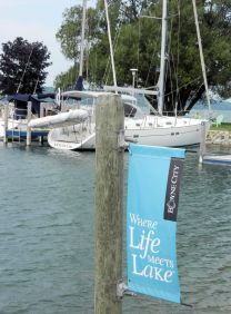 """a boat tied at a dock, a sign reads """"where life meets lake"""""""