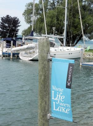 "a boat tied at a dock, a sign reads ""where life meets lake"""