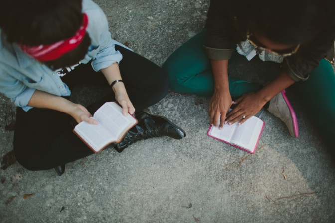two women sitting on the floor with open Bibles
