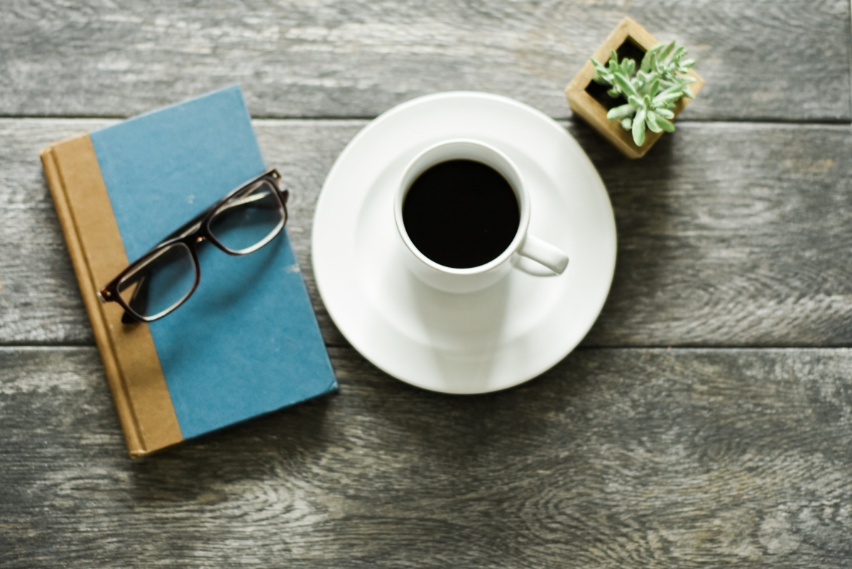 a book, reading glasses and cup of coffee on a table