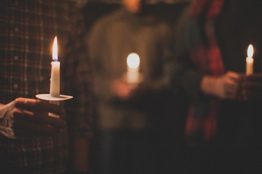 people holding lit candles in the dark