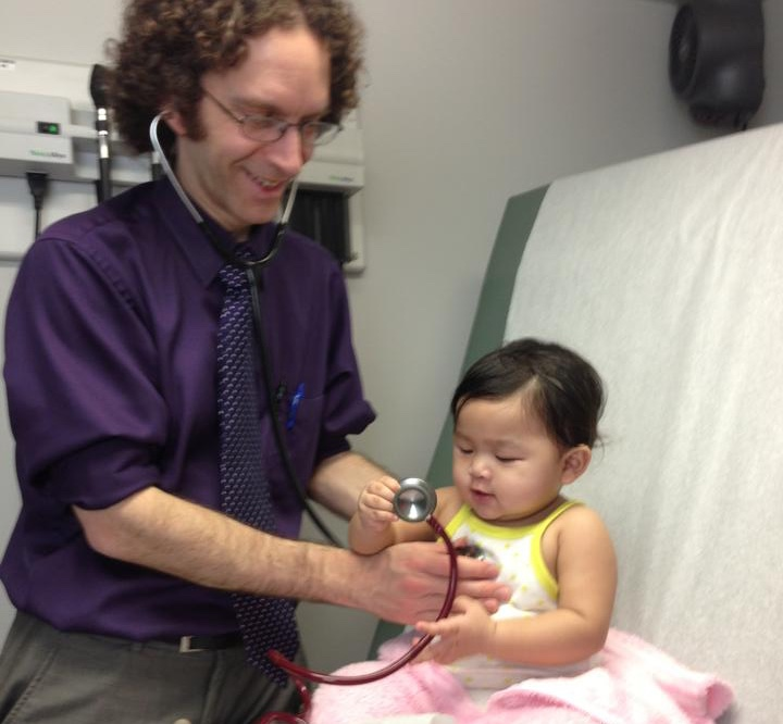 a male doctor examining a smiling baby girl
