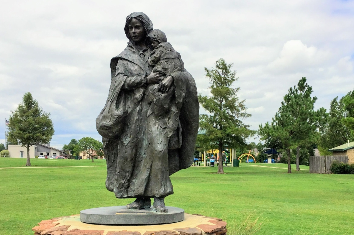 "a statue of a woman holding a child, ""CROSSING THE PRAIRIE"""