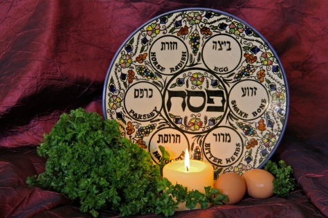 a Jewish passover seder plate with a lit cancle