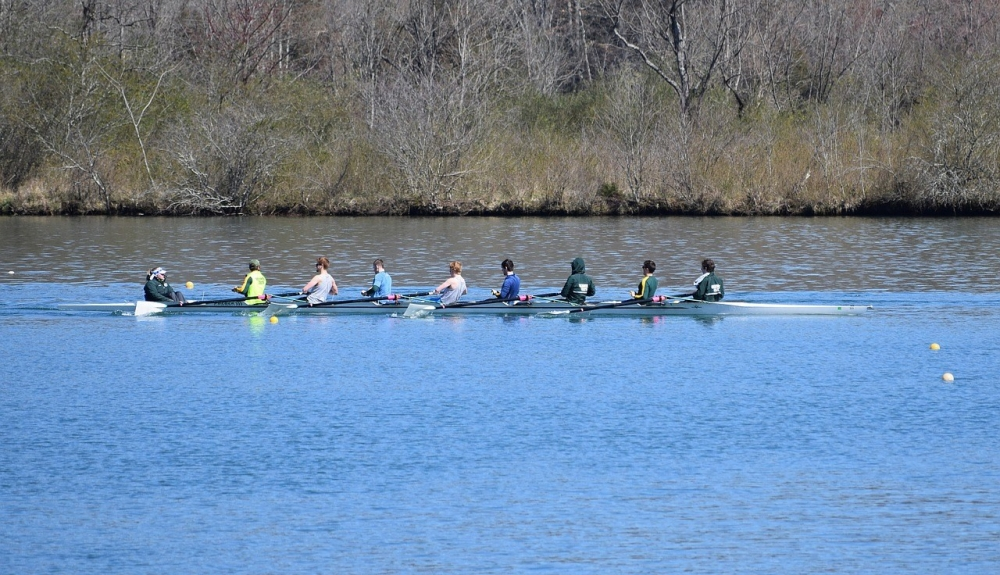 8 men rowing in a boat on a river
