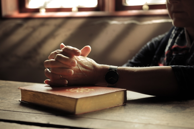 a man sitting with hands folded over a Bible