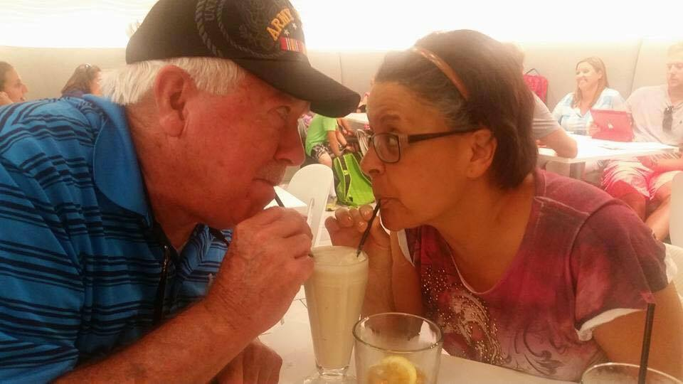 a couple sipping from a shake with two straws