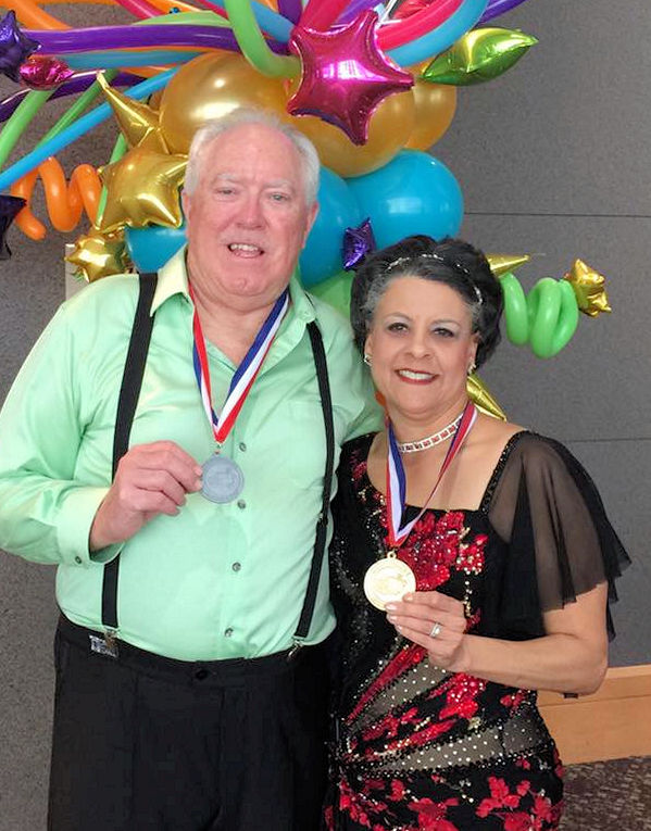 a couple in fancy clothes with medals around their necks