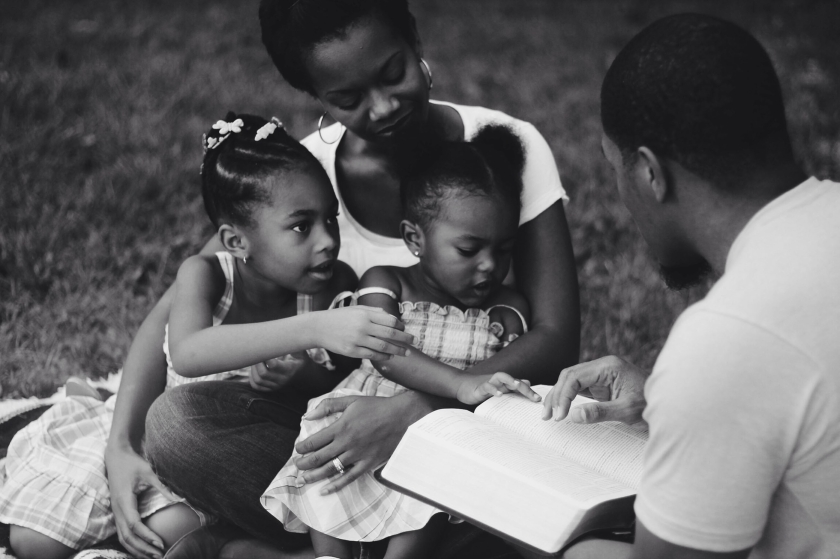 a man reading to two young girls, sitting in a woman's lap