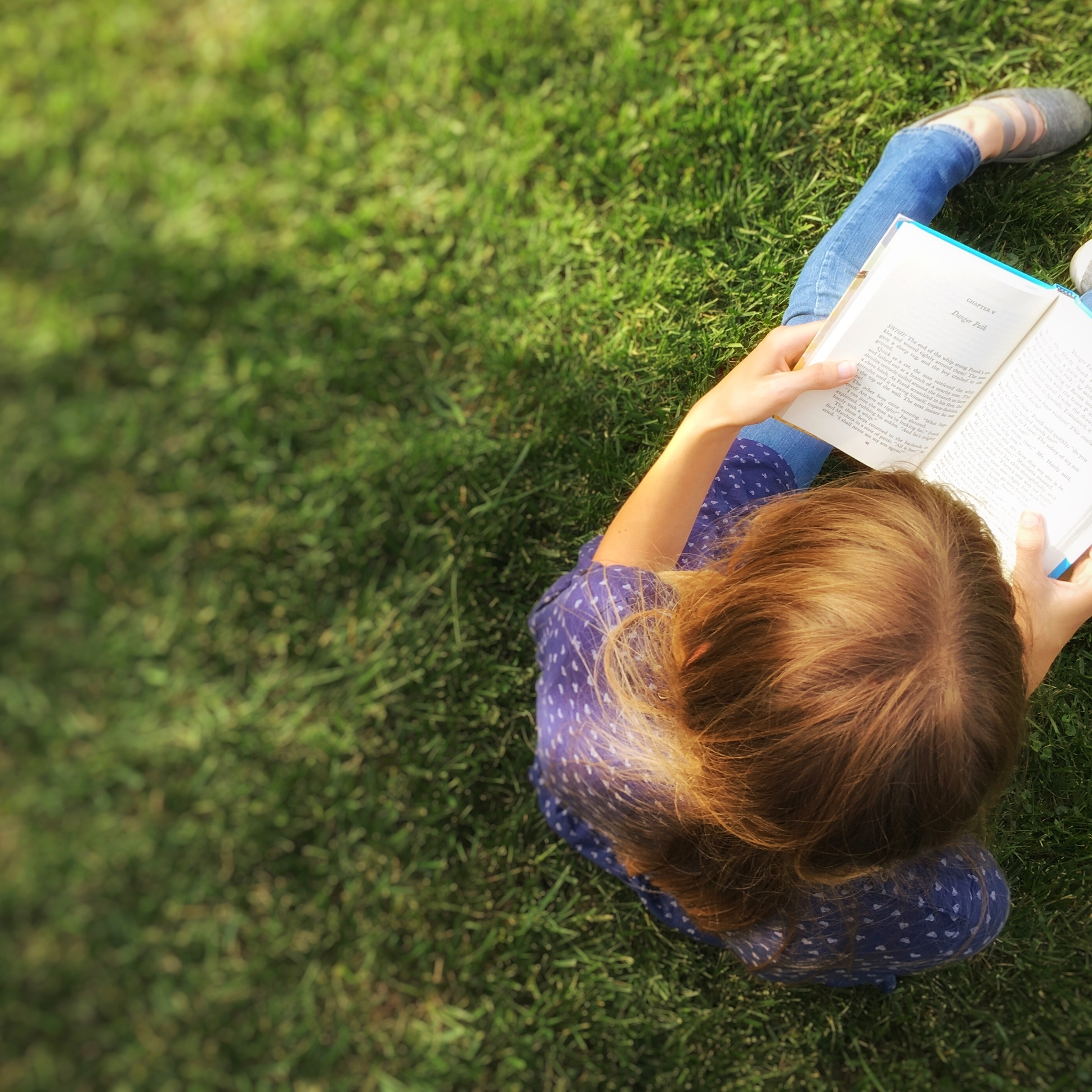 a girl sitting in grass reading a book.
