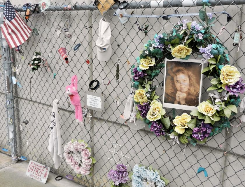 a chainlink fence with mementos-wreath, photo, flag, ball cap