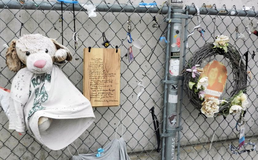 a chainlink fence with mementos-stuffed dog, wreath, photo, plaque