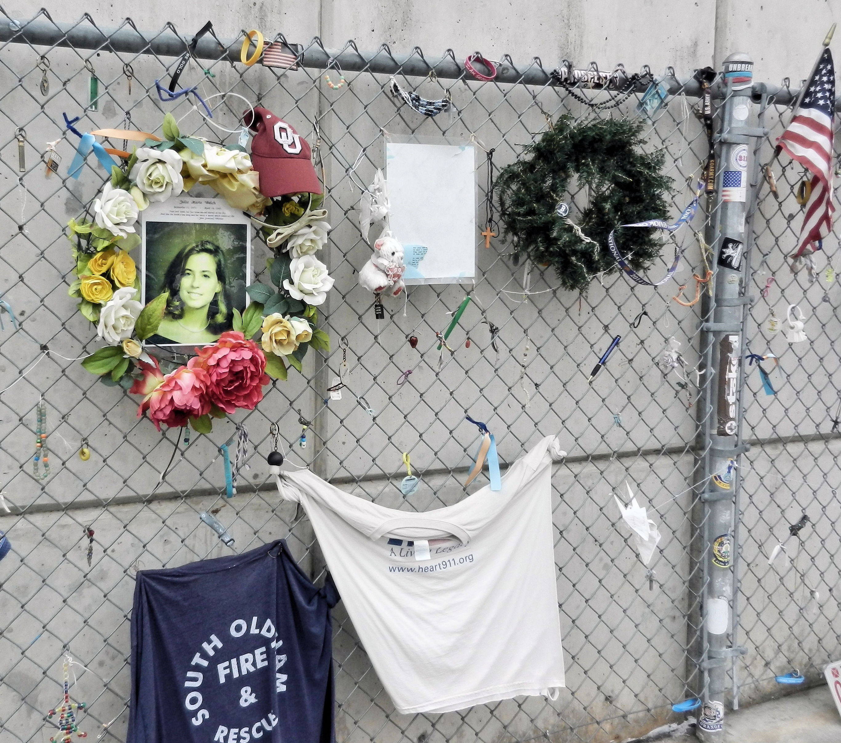 a chainlink fence with mementos-girl photo, teeshirts, wreaths, flag, toy