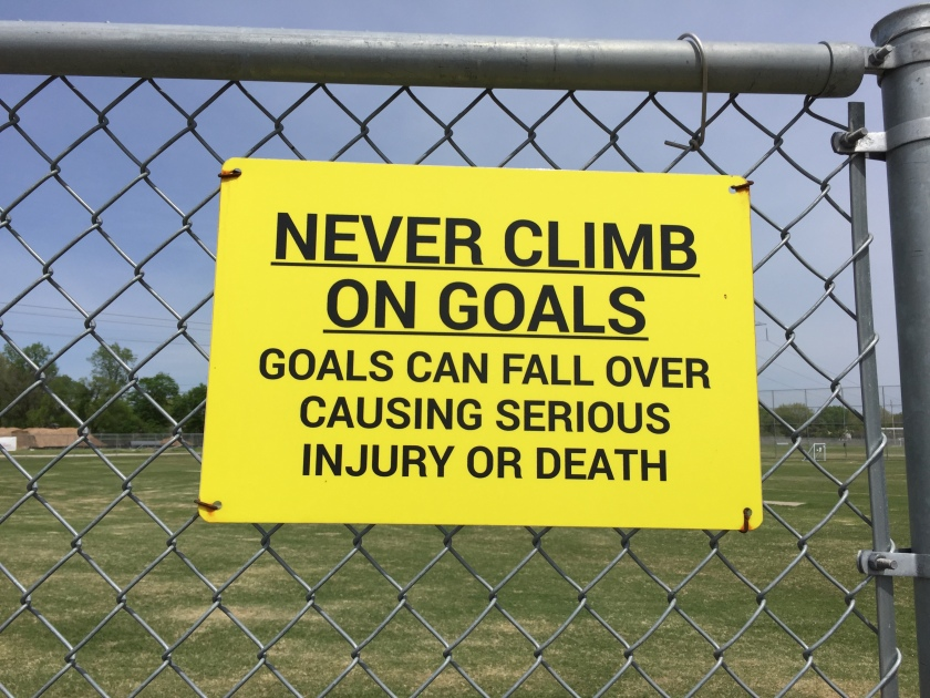 "a sign says""never climb on goals"""