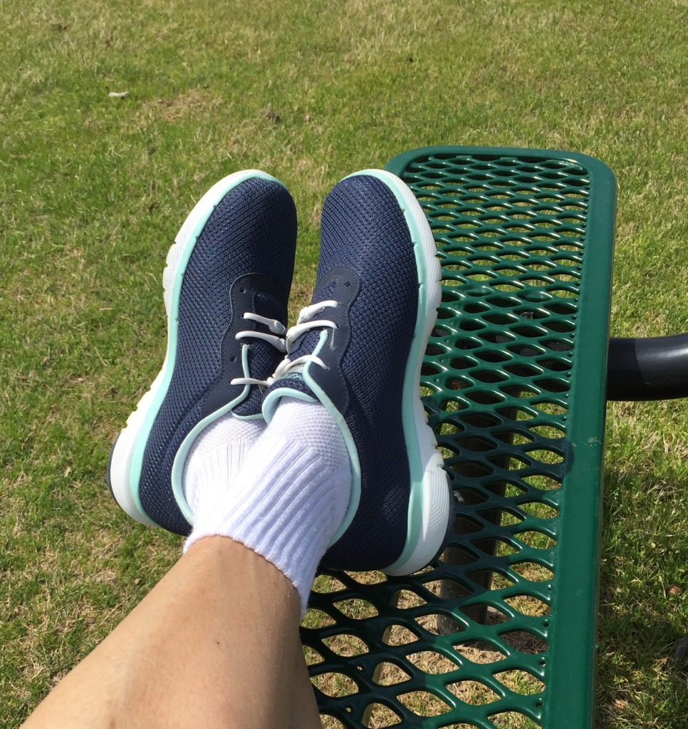 feet in walking shoes, crossed on a bench